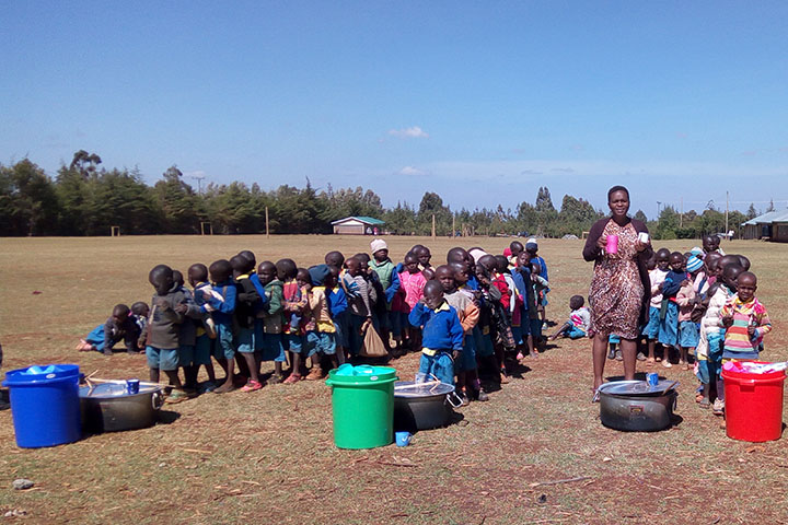 Porridge time: GREEiNSECT PhD student Carolyne Kipkoech serves porridge for school children in Uasin Gishu, Western Kenya. The children are randomized to receive either a plain porridge, or porridge with either insects (crickets) or milk. Photo: Afton Halloran